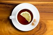 pic of brew  - Freshly brewed white cup and saucer of healthy herbal tea with lemon from above with heart shaped brown sugar cubes on a wooden table - JPG