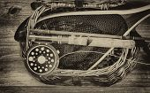 image of fly rod  - Vintage and aging grain concept of an antique fly fishing reel rod flies and net on top of open creel with rustic wood underneath - JPG