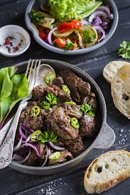 pic of liver fry  - fried chicken liver in a pan and grilled vegetables on a dark wooden background - JPG