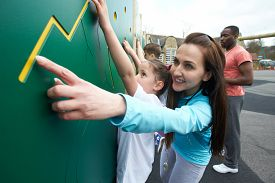stock photo of physical education  - Girl On Climbing Wall In School Physical Education Class - JPG