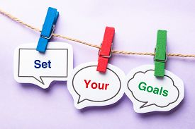 foto of bubble sheet  - Set your goals paper bubbles with clip hanging on the line against purple background - JPG