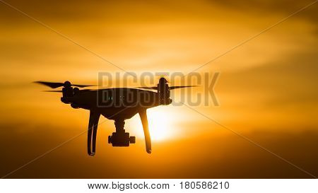 drone quad copter with digital camera at sunset ready to fly for surveillance. close-up of Rotor drones. 4 blade propeller drone. silhouette drone on sunset. Drone Video Camera. poster