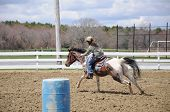 image of barrel racing  - A young teenage girl turns around a barrel and races to the finish line - JPG