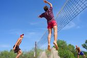 Three Men Playing Beach Volleyball - Teenager Jumps High With Splash Of Sand