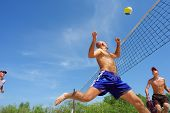 Постер, плакат: Четверо мужчин играть в пляжный волейбол лысеющий мужчина работает после мяча