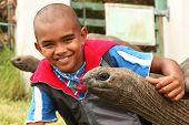 Smiling boy with giant tortoise