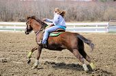 Young blonde teenager barrel racing