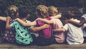 Group of kindergarten kids friends arm around sitting together poster
