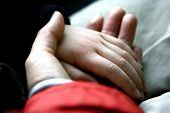 Child's hand resting tenderly in his mother's palm Concept: Nurture and Protect
