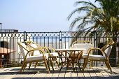 A table setting on a terraced lounge at a mediterranean resort hotel overlooking the sea