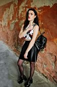 Young Goth Girl On Black Leather Skirt With Backpack Posed Against Grunge Wall. poster