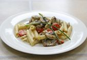 A plate of mushroom pasta and cream with tomatoes