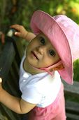 A pretty baby girl standing on a wooden park bench with a pink hat