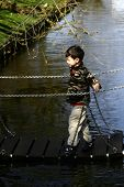 A young boy walks carefully on a wooden suspension bridge across a river