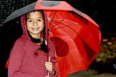A young girl standing under a red umbrella in the rain.