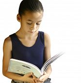 A young girl engross in her storybook, beautifully lit by the light from the window. Against white with copyspace.
