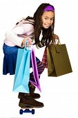 Girl of mix parentage with bags of shopping, zooming fast on a skateboard. Concept : Fast shopper