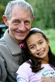 A young girl of mix parentage enjoying a cuddle with her grandfather. Concept: Love,appreciation and family value