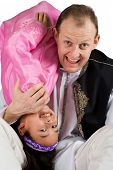 A girl throwing herself across her daddy's shoulder as they play together. Concept of love, joy and family bond.