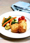 Salmon fishcakes served with steamed vegetables.