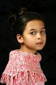 Portrait of a young girl of mix parentage, against black background.