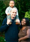 Beautiful family of inter-marriage couple having fun outdoors with toddler on father's shoulder.