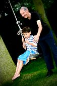 Grandfather pushing his grandson on the rope swing tied to a tree.