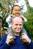 Beautiful baby boy sitting on his father's shoulder, in an outdoor setting.