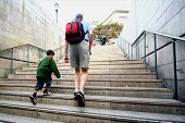 Father and son climbs up the stairs out from the train station in the city