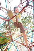 Young girl climbing giant web in playground activity