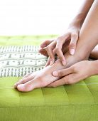 Female giving herself foot massage and reflexology.
