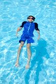 Young boy floats happily in a swimming pool