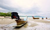 Long tail boats stranded on beaches at low tide along Krabi bay, Thailand.