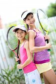 Two beautiful and fit sisters back to back with tennis racket each