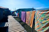 Wooden boardwalk with line of colorful washing in a water's village near Tuaran, Sabah Malaysia