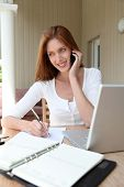 Self-employed woman at home talking on the phone
