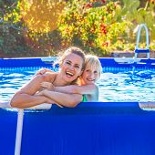 Happy Active Mother And Child In Swimming Pool Embracing poster
