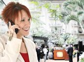 stock photo of opryland  - Beautiful thirty something caucasian redhead on cellphone at the Gaylord Opryland hotel in Nashville Tennessee - JPG