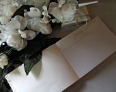 stock photo of funeral  - White flowers with a guest book on a linen surface - JPG