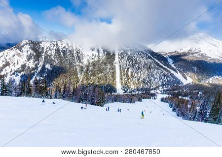 Unidentifiable Skiers And Snowboarders At