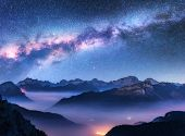 Milky Way Above Mountains In Fog At Night In Autumn. Landscape With Alpine Mountain Valley, Low Clou poster