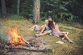 Friends Relax At Campfire. People At Bonfire Flame In Green Forest. Women And Man At Fire In Camp. C poster