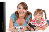 Mom and Daughter holding Joysticks and Playing Video Games on console together. Happy Family - Mothe poster