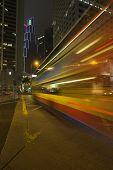Night bus lit by advertisement lights on Hong-Kong street