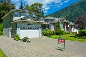 Suburban House In British Columbia For Sale. Big House With Wide Garage Door, Concrete Driveway, And poster