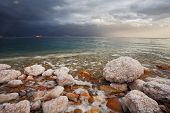 Winter on the Dead Sea. Blue storm cloud, green water and rocks, overgrown with salt