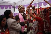 HARIDWAR, INDIA - JANUARY 14: Bride wears a wreath at the groom, which means their betrothal in a tr