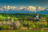 Gorgeous Spring Countryside Landscape, Church Of Hosman And High Snowy Fagaras Mountains In Backgrou poster