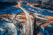 Aerial View Of Road In The Modern City At Night In Winter. Top View Of Traffic In Highway, Buildings poster