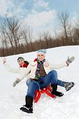 pic of toboggan  - Portrait of happy couple in warm clothes tobogganing in winter - JPG
